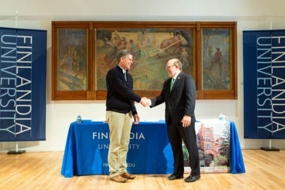 FinnU President Philip Johnson (left) and NMU President Fritz Erickson shake hands