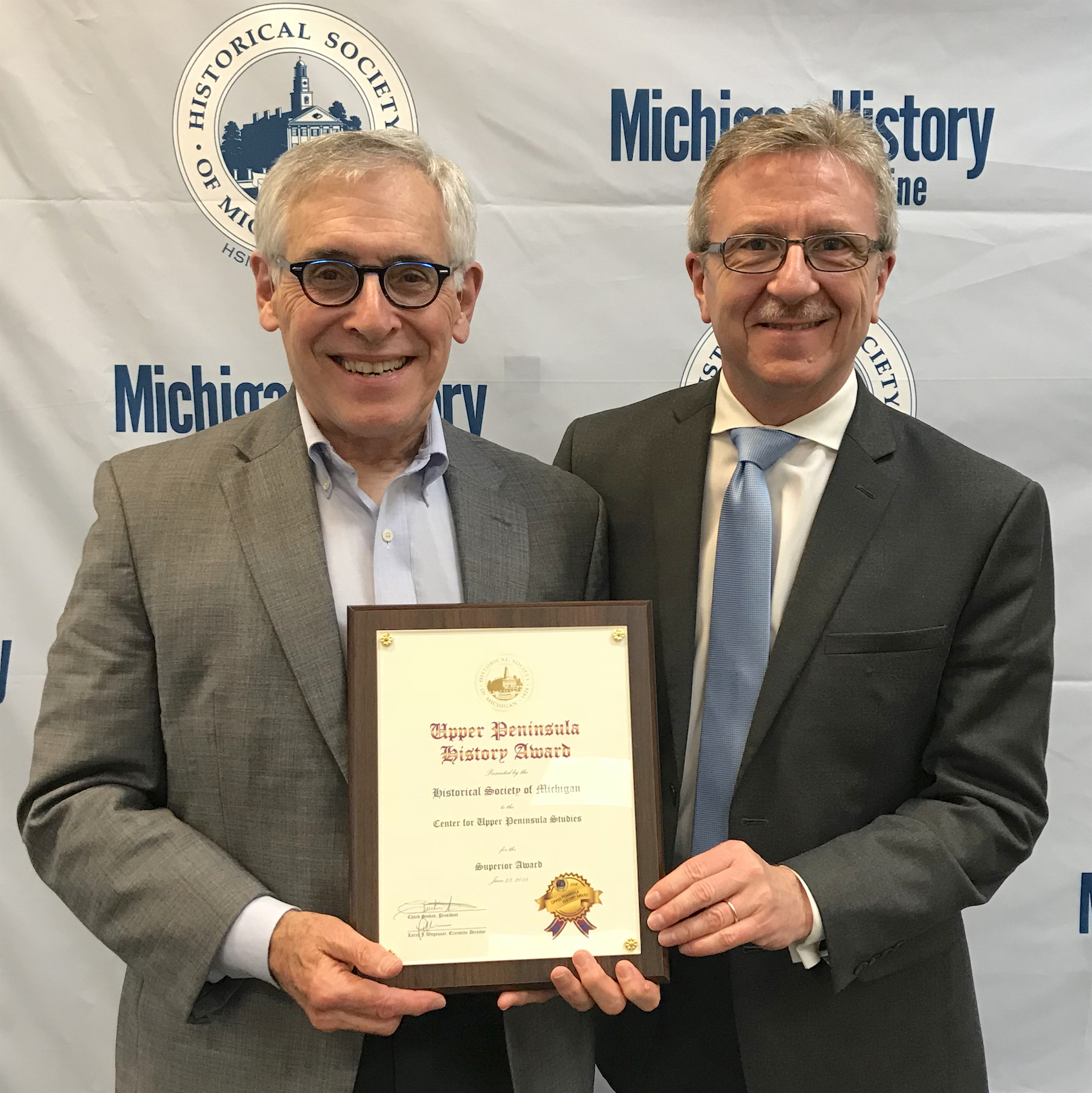 Magnaghi (left) accepting the award from Historical Society of Michigan Trustee Kendall Wingrove
