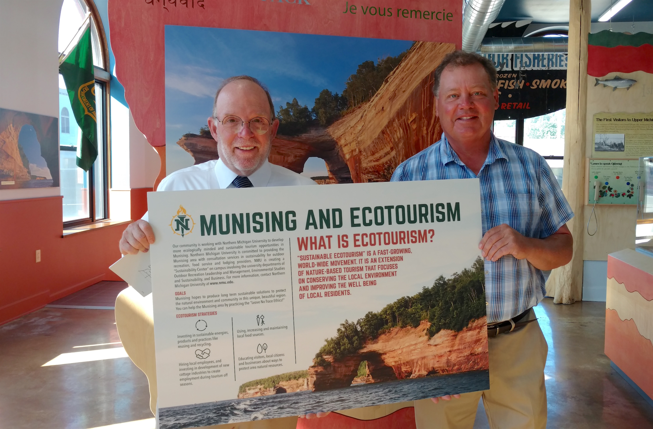 President Fritz Erickson delivered the ecotourism display piece to NMU alumnus John Madigan at the Pictured Rocks Interpretive Center.