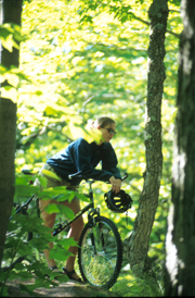 Mountain biking student resting on a trail near campus.