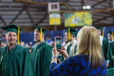 Mom taking a picture of son at graduation