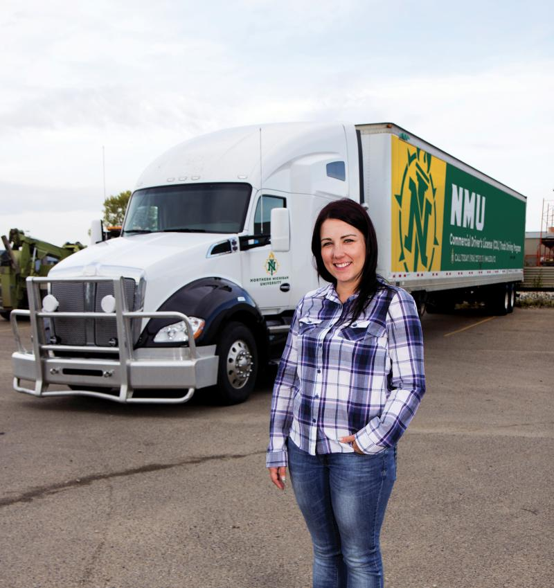 NMU female student poses in front of an NMU-branded semi