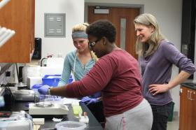 Students Natalie Yeck (left) and Rebecca Nyinawabeza with Teeter in the lab