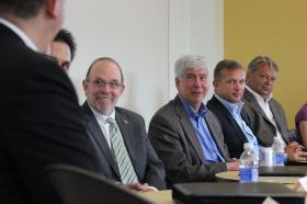 NMU President Fritz Erickson (with striped tie) sits next to Gov. Rick Snyder.