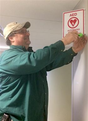 Trades specialist Gary Walimaa installs the AED in West Science