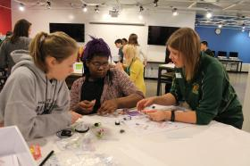 Renee Kivioja of the Seaborg Center helps students in a