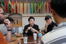 Lee (center) and other program participants talk with NMU students
