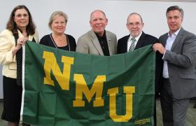 NMU officials present flag to honor Cliffs gift.