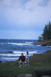 Two students biking by Lake Superior