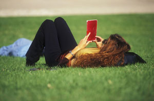 woman reading a book while laying on the grass