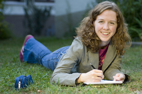 Female student on the grass writing