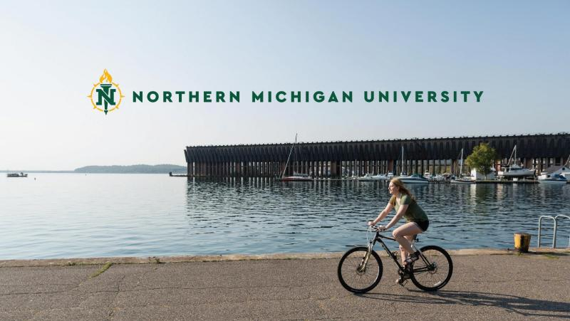 Student on a bike with the NMU logo over it